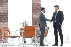 Two business people shake hands in the office Royalty Free Stock Images