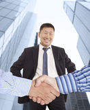 Business handshake. Between two colleagues on the background of happy asian businessman Royalty Free Stock Photos