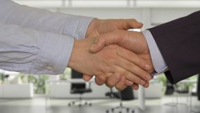 Business handshake with two hands after deal in office. Business handshake with two hands in modern office. Cropped view of businesswoman and businessman shaking stock video footage