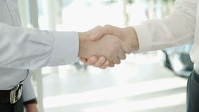 Business handshake of two men demonstrating their agreement. Sign agreement contract between their firms, companies, enterprises indoors. Close-up shooting of stock footage