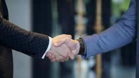 Business handshake of two men demonstrating their agreement. Sign agreement contract between their firms, companies, enterprises indoors. Close-up shooting of stock video footage