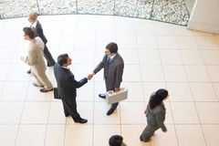 Business handshakes. Business men shaking hands and holding briefcases royalty free stock photography