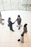 Business handshakes. Business men shaking hands in workplace royalty free stock images