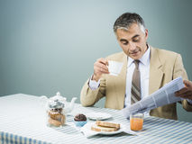 Business having a nutrient breakfast. Elegant businessman having a nutrient delicious breakfast and reading newspaper Royalty Free Stock Photo