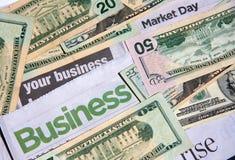 Business headline and money. Cash around business headline on newspaper Royalty Free Stock Image