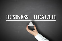 Business Health Balance. Concept with scale holden by businessman hand against the blackboard background Stock Images