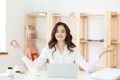 Business and Health Concept: Portrait young woman near the laptop, practicing meditation at the office desk, in front of. Laptop, online yoga classes, taking a stock photos