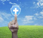 Business healthy and medical care insurance concept. Hand pressing cross shape with shield flat icon over green grass field with blue sky, Business healthy and royalty free stock images