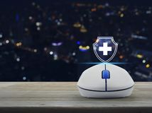 Business healthy and medical care insurance online concept. Cross shape with shield flat icon on wireless computer mouse on wooden table over blur colorful night royalty free stock photos