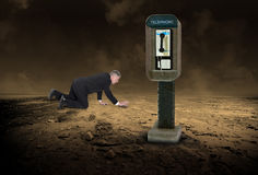 Business Help, Sales, Marketing, Trouble. Help is just a phone call away! A businessman crawls through a desolate desert but fails to see a pay telephone Royalty Free Stock Photo