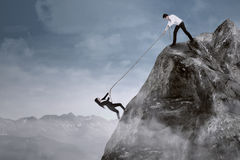 Business help to overcome adversity. Portrait of businessman help his partner to climb the cliff by pulling her with a rope Stock Photos