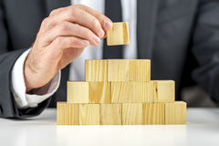 Business hierarchy concept. Closeup of businessman making a pyramid with empty wooden cubes. Concept of business hierarchy and human resources Stock Images