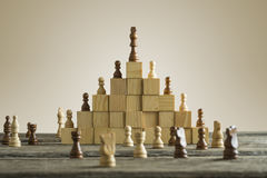 Business hierarchy; ranking and strategy concept. With chess pieces standing on a pyramid of wooden building blocks with the king at the top with copy space stock photo