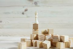 Business hierarchy. Strategy concept with chess pieces. Chess standing on a pyramid of wooden building blocks with the king at the top. copy space Stock Image