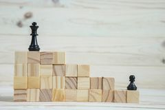 Business hierarchy. Strategy concept with chess pieces. Chess standing on a pyramid of wooden building blocks with the king at the top. copy space Stock Photos