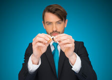 Business holding a broken cigarette Stock Photos