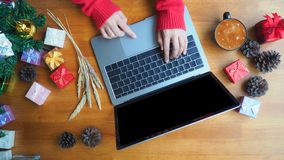 Business holiday online shopping concept. Business woman hand using laptop computer with blank screen on wooden desk, christmas and happy new year online Stock Photo