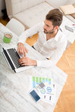 Business at home. A young man checking his business statistics at home stock photo