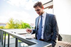Business, hot drinks and people and concept - young serious businessman with paper coffee cup over office building. stock images