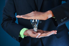 Business idea. Businessman holding light bulb. Royalty Free Stock Photo