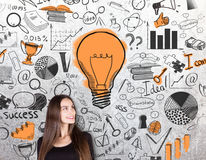 Business idea concept. Gorgeous caucasian female on concrete background with creative success sketch and light bulb. Business idea concept Royalty Free Stock Photo