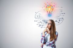 Business idea concept. With young thinking woman in glasses with colorful 3d bulb illustration above the head and ideas sketch on white wall background royalty free stock image