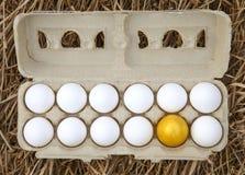 Gold egg with white egg. Business idea, golden egg in white dozen egg Stock Photos