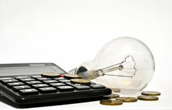 Business idea. Light bulb and coins on the calculator stock image