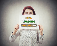 Business idea loading. Businesswoman, with a happy emotion, hiding face behind a white paper with a loading bar symbolizing business idea load percentage,  on Stock Images