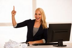 Business idea and success - woman behind the desk in office poin. Ting up in copy space as gesture of good results Royalty Free Stock Image