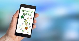 Business ideas concept on a smartphone. Hand holding a smartphone with business ideas concept Stock Photo