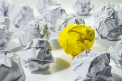 Ideas concept with yellow crumpled paper ball. stock photos