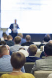 Business Ideas and Concepts. People at the Business Conference Listening to the Speaker Standing in Front of a Big Board on Stage Stock Photos