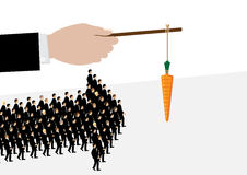Business Incentive. A large hand holds a carrot on a stick while his employees follow it in the shape of an arrow. A metaphor on management and leadership Royalty Free Stock Photo