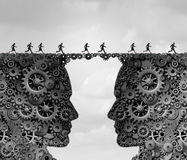 Business Industry Bridge. As a group of people running across a link made of gears and cogwheels shaped as a head as a success metaphor for technology solutions Royalty Free Stock Photos