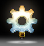 Business Innovation. And creativity as a light bulb illuminated glass in the shape of a gear or cog as a concept of creative success in innovative ideas for Stock Images