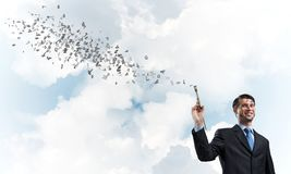 Business inspiration of young man. Successful and confident businessman keeping paintbrush in his hand while standing with flying letters against cloudy skyscape Stock Image