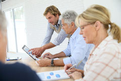 Business instructors with seniors using tablet. Business instructor with group of senior people Stock Photos