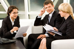 Business interaction. Portrait of three white collar workers discussing a new idea Royalty Free Stock Photo