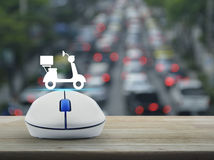 Business internet delivery service concept. Motor bike icon with wireless computer mouse on wooden table over blur of rush hour with cars and road, Business Royalty Free Stock Images