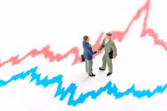 Business investment and finance concept. Miniature people figurines businessmen stand on finance graph royalty free stock photos