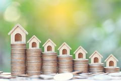 Business investment and real estate concept, Growing model house on stack of coins money on natural green background royalty free stock image