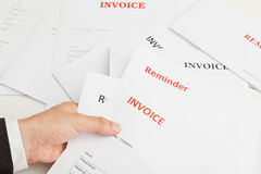 Business invoices. Business man holding numerous invoices and reminders Royalty Free Stock Images