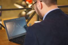 Man in glasses watches the falling exchange chart on the laptop stock photos