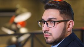 Portrait young man trader with a beard in glasses in cafe royalty free stock images