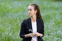 Business jacket and white top, carefully looks to the side, in her hands a small bouquet of forget-me-nots. royalty free stock images