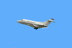 Business jet. Taking off isolated over blue Stock Photography