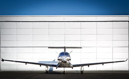 Business Jet. A small private business jet parked in front of a hangar Stock Image