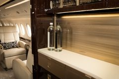 Business jet aircraft cabin interior. Luxury VIP business jet aircraft cabin interior seat and kitchen royalty free stock images