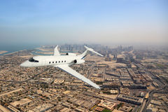 Business jet airplane flying over city. Business jet airplane flying over city on clear day Royalty Free Stock Photo